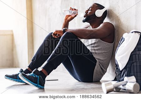 Tired bearded well-build athlete is sitting on floor, drinking water and listening to music. Fosuc on headphones and bottle with water