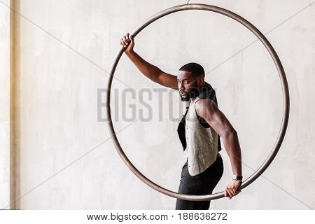 Portrait of pensive handsome man standing near big metal ring. He is wearing trendy waistcoat on naked body