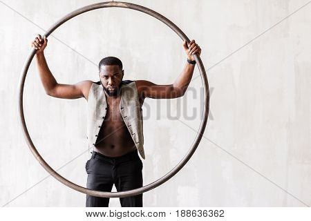 Full length portrait of angry handsome muscular man standing in center of big metal ring in trendy clothing. His vest is unbutton and his torso is naked