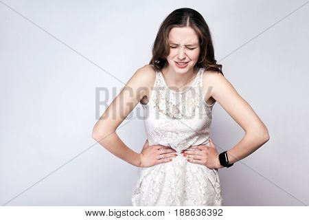 Portrait of beautiful woman with freckles and white dress and smart watch with stomach pain on silver gray background. healthcare and medicine concept.