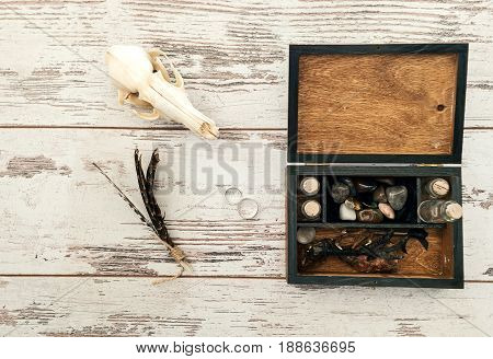 Wooden Box With Wedding Rings, Bird's Paws, Feathers, Empty Bottles And Stones On Wooden Background,