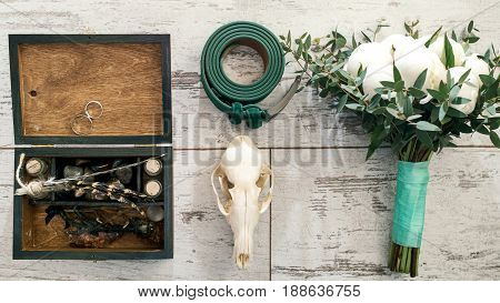 Top View Of Green Groom's Belt, Skull, Wedding Bouquet Of White Peony, Wooden Box With Wedding Rings