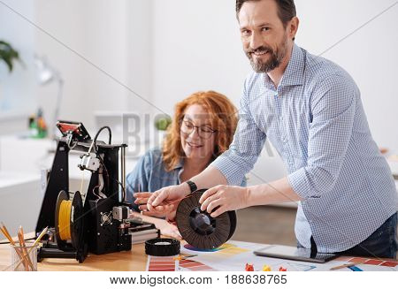 Interesting job. Cheerful handsome positive designer looking t you and smiling while leading filament into the 3d printer