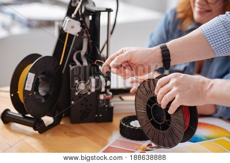 3d modeling. Selective focus of a filament coil being in hands of a professional male 3d designer
