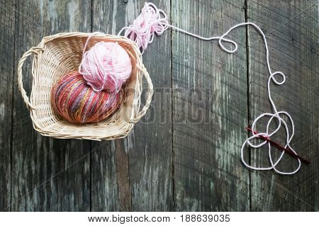 Two balls of yarn in square basket with trailing strand of yarn and crochet hook. Background of rustic wood planks