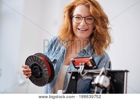 Filament coil. Joyful happy nice woman holding a filament coil and looking at you while working as a 3d designer