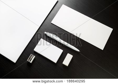 Photo of blank stationery on black wood table background. Envelope business cards pen letterhead sharpener and A4 paper. Top view.