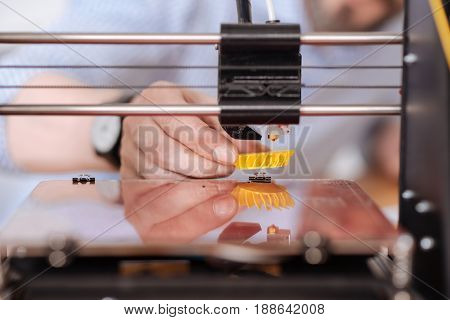 Printing process. Close up of a small yellow 3d model being printed on a special 3d printing machine