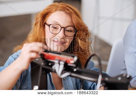 Innovative type of printing. Professional smart positive designer looking at the printing machine and doing the setting of it while testing 3d technology