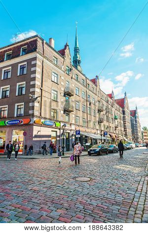 Street With People And Spire Of Saint Peter Church Riga