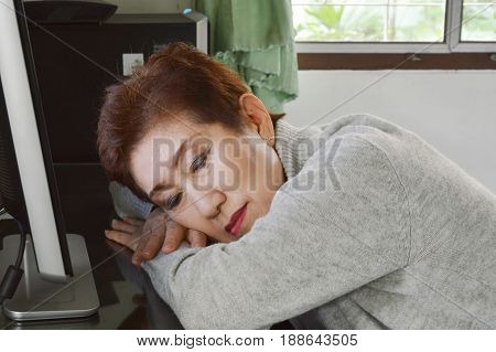Asian elder woman take a nap on desk in front of personal computer