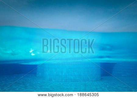 Half underwater shot clear turquoise water on swimming pool and clear sky.