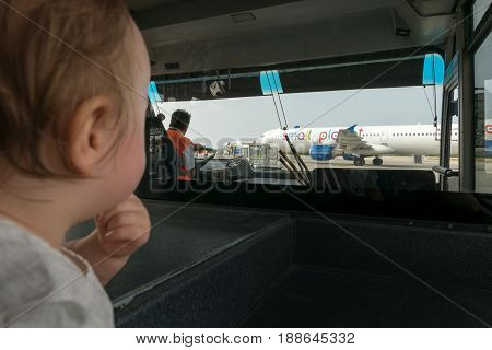 Kos island Greece - 13 May 2017: Baby look at the plane from bus cabine she's very fascinated by the view.