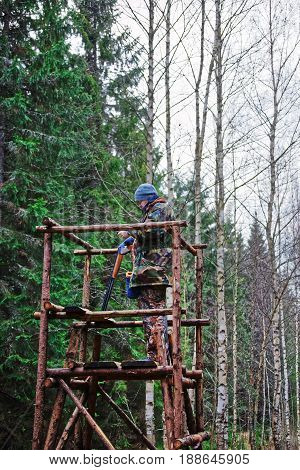 Male Hunter On Watch Tower In Autumn Forest
