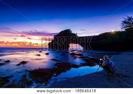 professional photographer with camera and tripod in Tanah Lot Temple at sunset Bali in Indonesia.(Dark)Seascape.