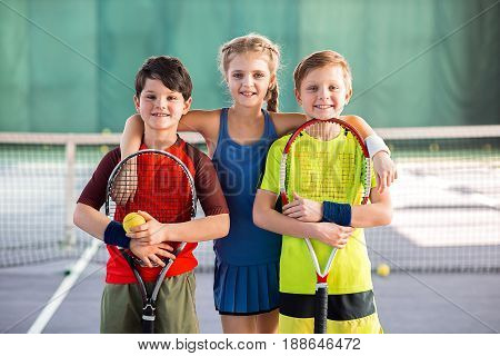 We like tennis. Happy girl is embracing two boys while standing on playground. They are holding tennis racquets and smiling. Portrait