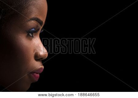 Side view portrait of dark skinned model on a black background. Close up portrait of dark skinned female with bright make up. Side view portrait of beautiful model with bright make up.