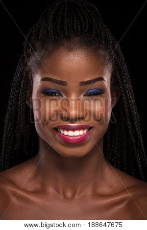 Smiling dark skinned model on a black background. Close up portrait of young dark skinned woman. Model with open smile showing white teeth.