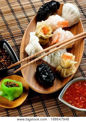 Various Dim Sum on Wooden Plate Red Chili and Soy Sauces and Chopsticks closeup on Straw Mat background