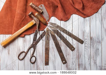 Set Of Cobbler Tools On The Light Wooden Background. Space For Text.