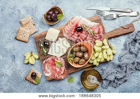 Typical italian antipasto, wooden cutting board with prosciutto, ham, cheese and olives on gray stone background. Top view with copy space
