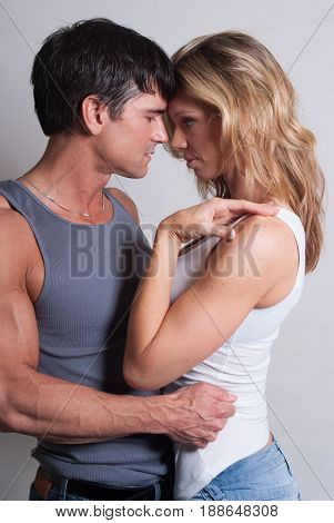 The extremely attractive couple is in a loving embrace.