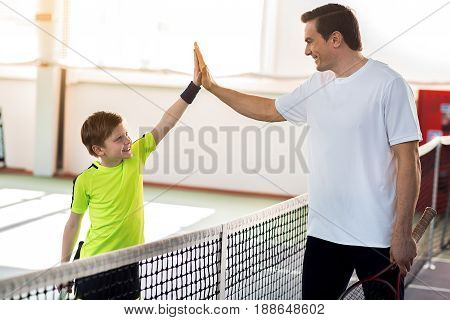 Cheerful boy is giving high five to his father after playing tennis. They are standing near net and laughing