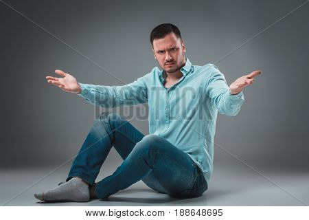 Handsome young man sitting on a floor with raised hands gesturing on gray background. A man in jeans and a blue shirt