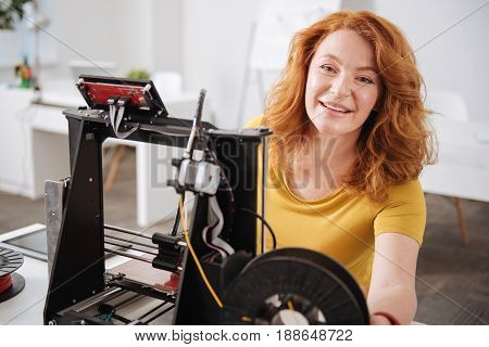 Interesting experience. Positive happy nice woman sitting in front of 3d printer and smiling while enjoying her work with 3d technology