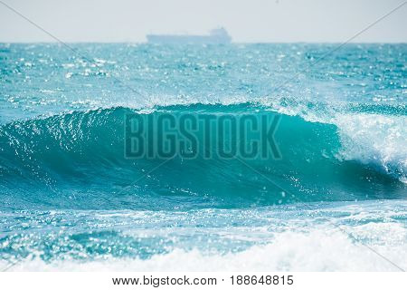Blue ocean wave in tropics. Wave barrel crashing and clear water.