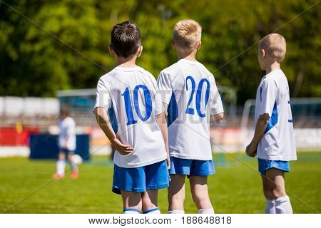 Youth Sport Soccer Team. Young Footballers as Substitute Players Watching Football Tournament Match. Boys Kicking Football Soccer Game in the Background