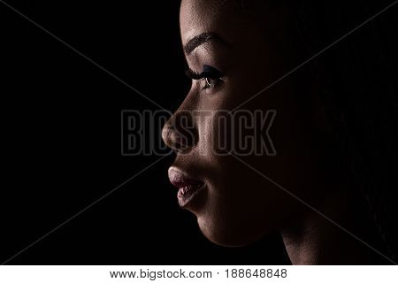 Side view portrait of dark skinned model on a black backstage. Light and shadow portrait of a woman in side view.