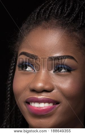 Close up portrait of dark skinned model on black backstage. Young dark skinned woman smiling showing teeth. Model with bright make up and smiling face.