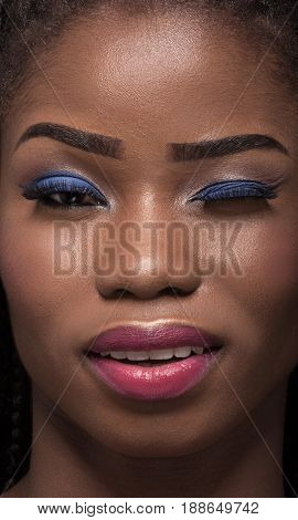 Close up portrait of dark skinned model with one eye closed. Smiling winking face of dark skinned young woman. Bright make up on dark skin.