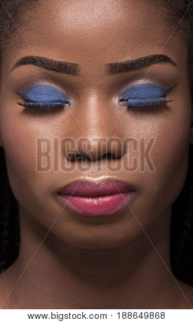 Close up portrait of dark skinned model with closed eyes on black backstage. Portrait of woman with bright make up and closed eyes.