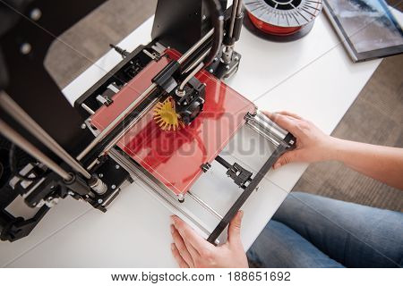 Printing 3d objects. Top view of a 3d printer being in use by professional designers while printing