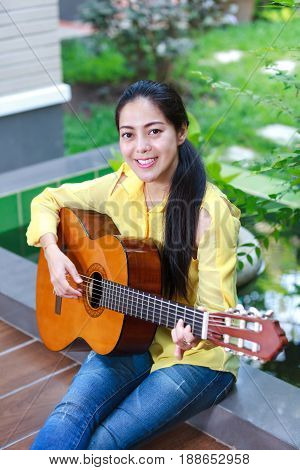 Asian Woman Playing Classic Guitar, Outdoor At Daytime With Bright Sunlight.