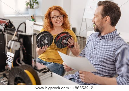 Which one is better. Delighted positive nice woman holding two filament coils and deciding which one to choose while asking advice from her colleague