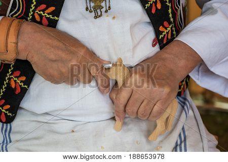 Woodcarver dressed in folk costume carves from wood - Folk art