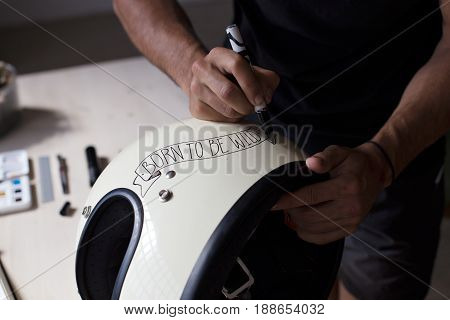 Hard working careful meticulous illustrator creates piece of art beige white helmet for motorcycle fair show draws inspirational quote on top with hand lettering