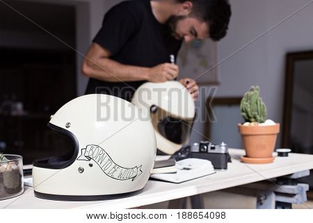 Young artisanal man perfects his craft of customization and decoration of objects with art of calligraphy and hand lettering paints with ink and oil over vintage helmets