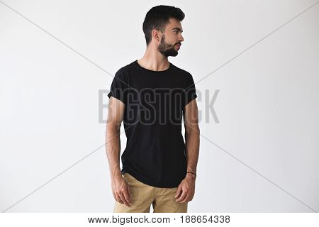 Handsome sporty strong man looks to the side posing in studio in blank simple black t-shirt and chinos shorts on isolated white mockup