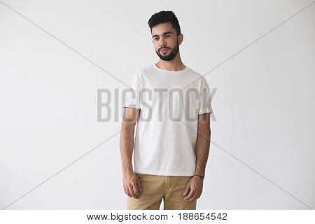 Front shot of hispanic or caucassian attractive hipster millennial male model softly smiling and wearing simple white blank t-shirt on isolated mockup background