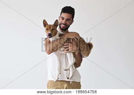 Happy laughing attractive male holds and hugs his best friend little basenji brown puppy dog who is licking his face after tasty meal