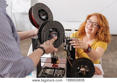 Give them to me. Delighted positive red haired woman looking at her colleague and taking filament coils while intending to use them for 3d printing