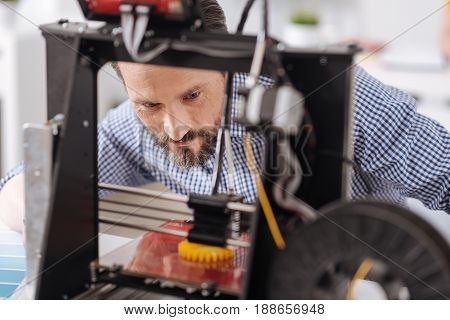 3D printing. Handsome serious male designer leaning over the 3d printing machine and watching how it works while concentrating on his job