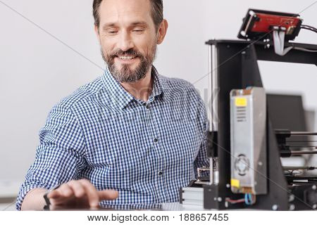 My favourite job. Delighted successful male designer smiling and working with a 3d printing technology while being happy about his job