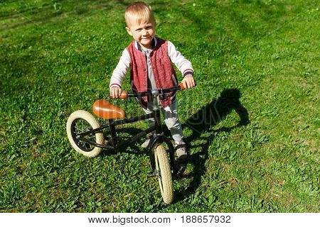 Child with run bicycle on green lawn in park during day