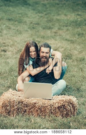 man or happy guy with winner gesture and pretty girl or cute woman with long hair using laptop on hay bale on grass on summer day on natural background. Couple in love. Technology nature