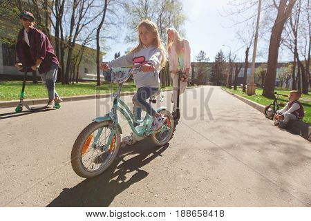 Girl with family on rides bicycles in park